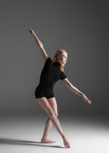 young beautiful modern style dancer posing on a studio gray background