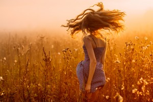Dancing beautiful girl in fog, field, sun backlight, sunrise, orange colors