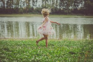 little girl with long blond hair in pink dress dancing at midnight in the green grass by the river