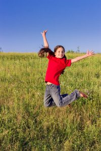 Happy jumping girl on green field, outdoors