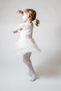 Little cute blonde ballerina at ballet training on white background